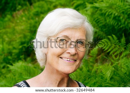 Senior woman portrait, outdoor, in front of fern,smiling to camera - stock photo