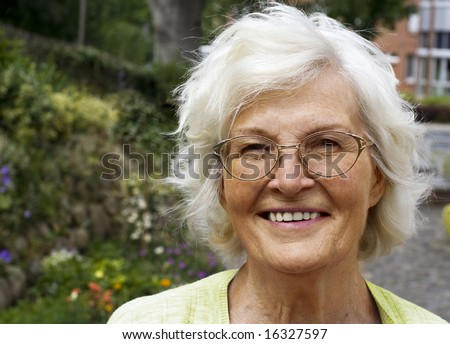 Senior woman portrait, outdoor in front of house and garden - stock photo