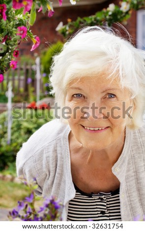 Senior woman portrait, outdoor, in front of the garden,smiling to camera - stock photo
