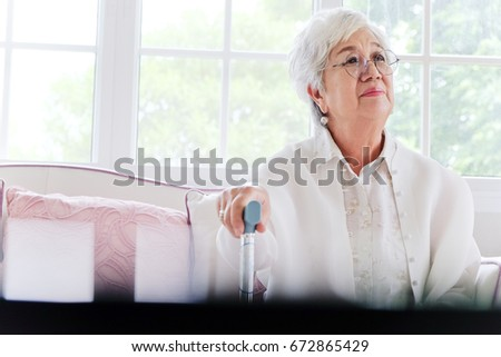 senior woman portrait, senior woman sitting alone on a sofa at home in a lonely mood.