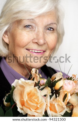 Senior woman portrait, smiling with a bunch of roses - stock photo