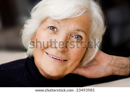 Senior woman portrait, smiling with hand on neck - stock photo