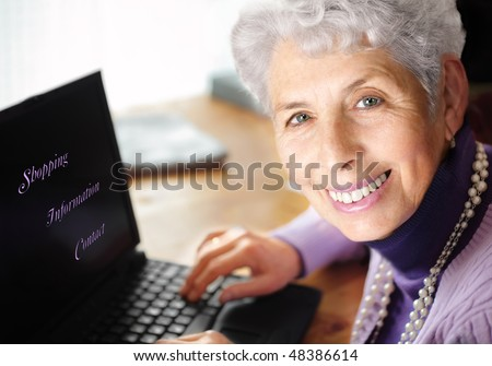"Senior woman portrait, typing on laptop and smiling great at camera. With text on laptop:""Shopping, Information,Contact"" - stock photo"