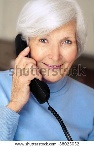 Senior woman portrait  with white hair and blue pullover holding phone receiver - stock photo