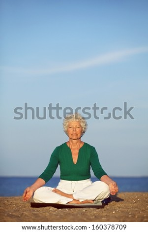 Senior woman practicing morning yoga with ocean in background. Old caucasian woman doing relaxation exercise on beach. Meditation, yoga and relaxation concept. - stock photo