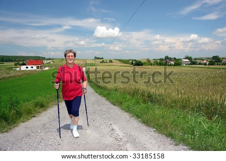 Senior woman practising nordic walking in the countryside - stock photo