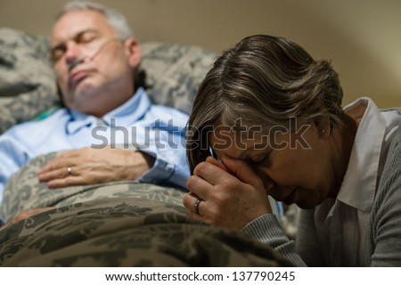 Senior woman praying for sick man sleeping in hospital bed - stock photo