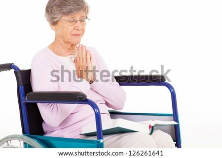 senior woman praying on wheelchair isolated on white - stock photo