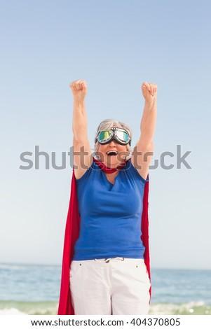 Senior woman pretending to be a superhero on a sunny day - stock photo