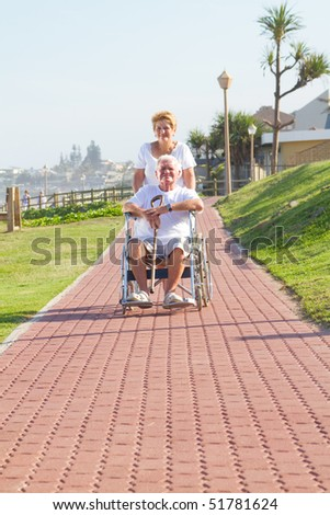 senior woman pushing her disabled husband on wheelchair - stock photo