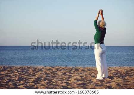 Senior woman raises her arms over her head in a stretching position while standing by the sea at morning. Old woman exercising on the beach - stock photo