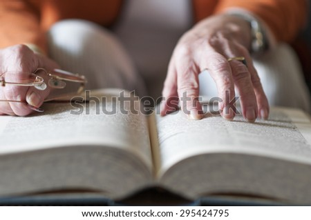 Senior woman reading a book and in her hand she holds a pair of eyeglasses.