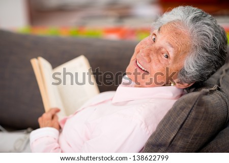 Senior woman reading a book at home enjoying her retirement - stock photo