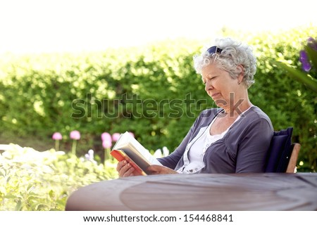 Senior woman reading a book sitting outside on a chair at the garden. Elder woman reading novel at her backward garden - stock photo