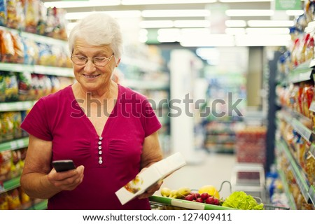 Senior woman reading a message on mobile phone at supermarket - stock photo