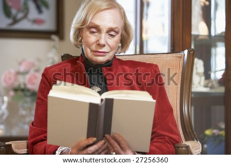 Senior woman reading book - stock photo