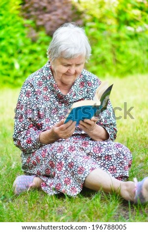 Senior woman reading book in park. MANY OTHER PHOTOS FROM THIS SERIES IN MY PORTFOLIO. - stock photo