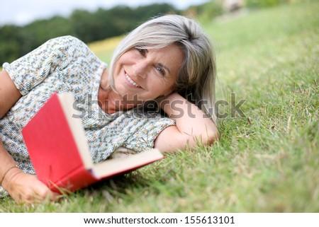 Senior woman reading book laid on the grass - stock photo