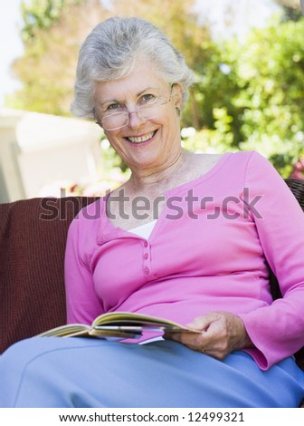 Senior woman reading book outside looking to camera - stock photo