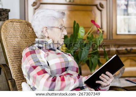 Senior woman reading book relaxed at home - stock photo