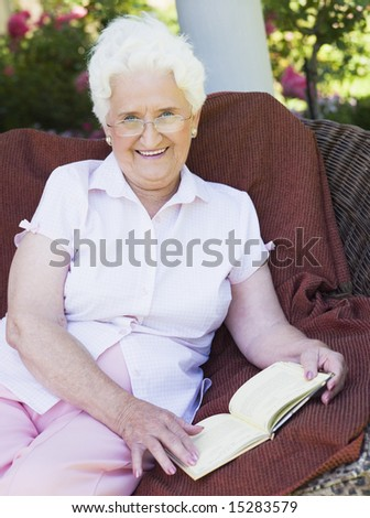 Senior woman reading book sitting on garden chair - stock photo