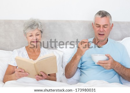 Senior woman reading book while man having cereals in bed at home - stock photo