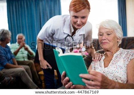Senior woman reading book with nurse in the retirement house