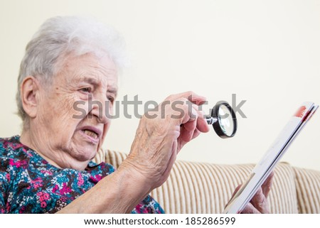 senior woman reading by using a magnifying glass - stock photo