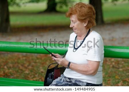 Senior Woman reading E-Book reader on bench  - stock photo