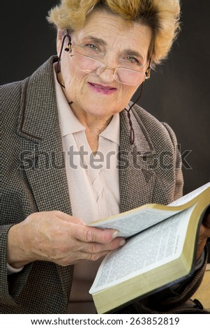 Senior woman reading holly bible. Woman with glasses. Black backgground