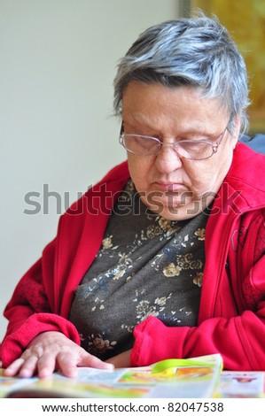senior woman reading magazine - stock photo