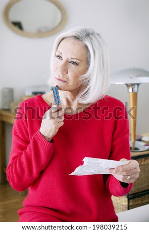 Senior woman reading medication instruction sheet. - stock photo