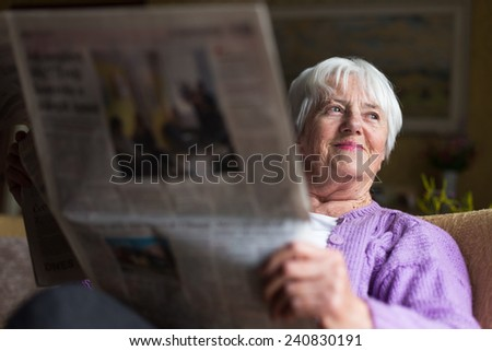Senior woman reading morning newspaper, sitting in her favorite chair in her living room, looking happy - stock photo
