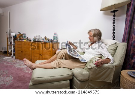 Senior woman reading newspaper while relaxing on armchair at home - stock photo