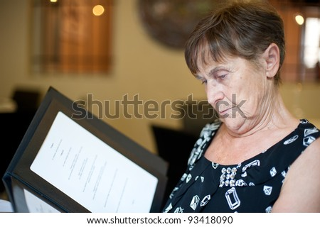 Senior Woman reading the menu at the restaurant - stock photo