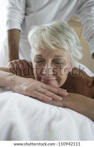 Senior woman receiving back massage at resort spa - stock photo