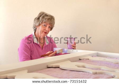 Senior woman refinishing and repainting old furniture to be used in home, saving money by doing it herself and recycling old furniture. Horizontal shot with large foreground. - stock photo