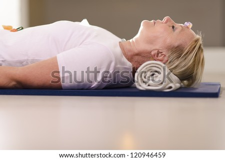 Senior woman relaxing and lying on pad with amethyst, quartz and other crystals on body. Side view, copy space - stock photo
