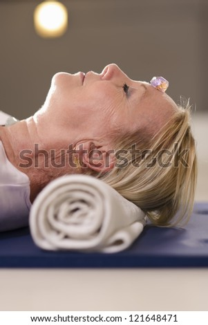 Senior woman relaxing and lying on pad with amethyst, quartz and other crystals on body. Side view - stock photo