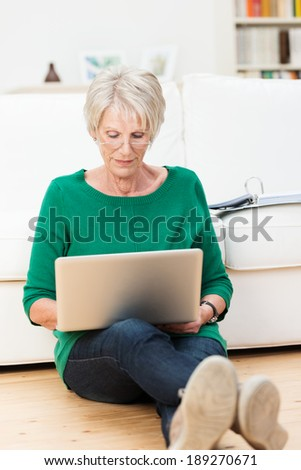 Senior woman relaxing at home with a laptop computer sitting on the hardwood floor in the living room with her back to the sofa concentrating on her work - stock photo