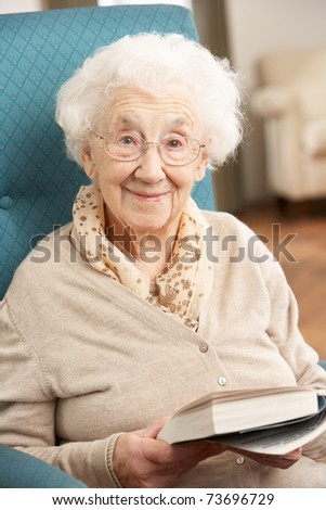Senior Woman Relaxing In Chair At Home Reading Book - stock photo