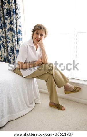 Senior woman relaxing in her bedroom - stock photo