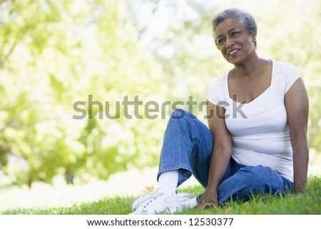 Senior woman relaxing in park sitting on grass - stock photo