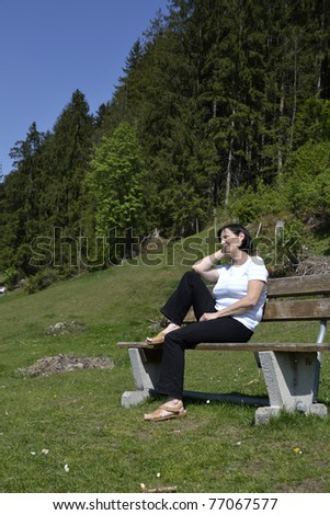 Senior woman relaxing on bench in austrian forest.