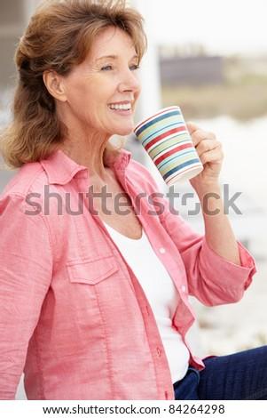 Senior woman relaxing outdoors - stock photo