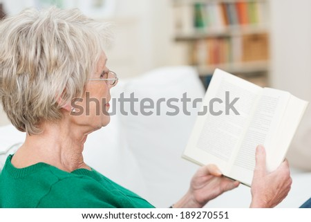 Senior woman relaxing reading a book on a sofa at home, over the shoulder view - stock photo