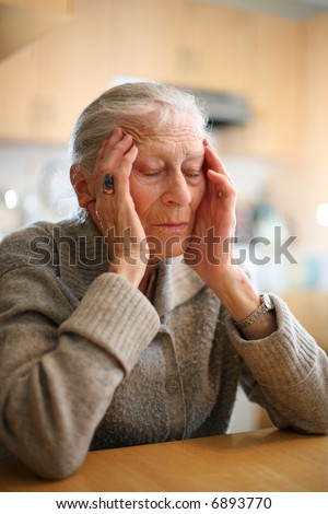 Senior woman relaxing to end headache. Shallow DOF. - stock photo