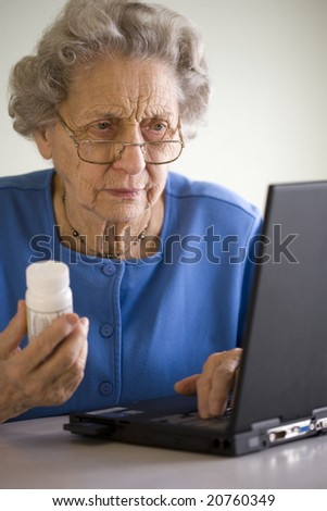 Senior woman researching prescription  on-line - stock photo