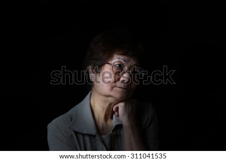 Senior woman resting her chin with one hand while displaying loneliness on black background. Depression concept.