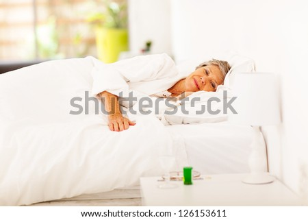 senior woman resting on bed at home - stock photo